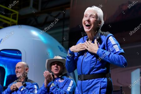Mark Bezos, left, and Jeff Bezos, center, founder of Amazon and space tourism company Blue Origin, applaud as Wally Funk, right, describes their flight experience from the spaceport near Van Horn, Texas