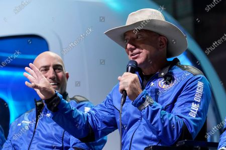 Mark Bezos, left, listens as his brother Jeff Bezos, founder of Amazon and space tourism company Blue Origin, describes the flight experience after their launch from the spaceport near Van Horn, Texas