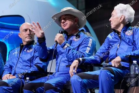Mark Bezos, left, and Wally Funk, right, listen as Jeff Bezos, center, founder of Amazon and space tourism company Blue Origin makes comments about their flight experience during a post launch briefing at its spaceport near Van Horn, Texas