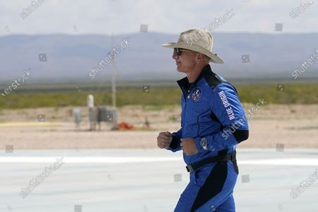 Jeff Bezos, founder of Amazon and space tourism company Blue Origin jogs onto the Blue Origin's New Shepard rocket landing pad to pose for photos at the spaceport near Van Horn, Texas