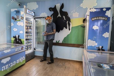 """An Israeli shops at the Ben & Jerry's ice-cream factory in the Be'er Tuvia Industrial area, . Israeli Prime Minister Naftali Bennett told the head of Unilever on Tuesday that Israel will """"act aggressively"""" against Ben & Jerry's over the subsidiary's decision to stop selling its ice cream in the Israeli-occupied West Bank and contested east Jerusalem"""