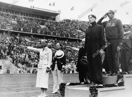 Gold medalist Jessie Owens, second right, salutes during the playing of the national anthem during the medal ceremony of the 100-meter final in Berlin. silver medalist Tinus Osendarp, third from right, of, Holland, and bronze medalist Ralph Metcalf, right, listen, along with a matron who holds a Nazi salute. The 1936 Games in Berlin, awarded about two years before Adolf Hitler became dictator, went ahead under Nazism. American track great Jesse Owens went on to win four gold medals, but he was only supposed to compete in three events, the 100 meters, 200 meters and long jump