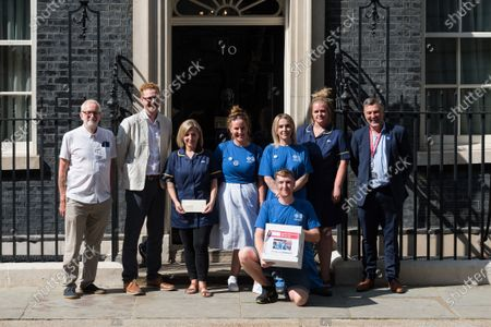 Stock Photo of LONDON, UNITED KINGDOM - JULY 20, 2021: Jeremy Corbyn MP (1L) and Ian Byrne MP (1R) together with NHS staff deliver a petition with 800,000 signatures to 10 Downing Street demanding 15% pay increase for health workers on July 20, 2021 in London, England. The Department for Health and Social Care has recommended that NHS staff in England should receive a 1% pay increase this year despite the unprecedented pressure experienced by the health workers during the coronavirus pandemic.