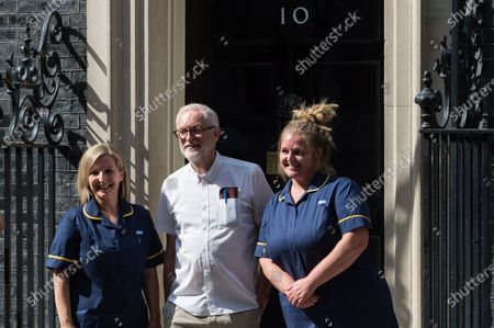 Stock Picture of LONDON, UNITED KINGDOM - JULY 20, 2021: Jeremy Corbyn MP (C) poses for pictures outside 10 Downing Street after delivering together with NHS staff a petition with 800,000 signatures demanding 15% pay increase for health workers on July 20, 2021 in London, England. The Department for Health and Social Care has recommended that NHS staff in England should receive a 1% pay increase this year despite the unprecedented pressure experienced by the health workers during the coronavirus pandemic.