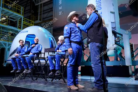 Oliver Daemen, from left, Mark Bezos and Wally Funk, look on as Jeff Bezos, second from right, is awarded his Blue Origin made astronaut wings by former NASA astronaut, Jeff Ashby, right, who is now based with Blue Origin, during a New Shepard post launch briefing at the spaceport near Van Horn, Texas