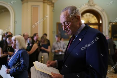 Senate Majority Leader Chuck Schumer, D-N.Y., joined at left by Assistant Majority Leader Patty Murray, D-Wash., looks over his notes as he talks to reporters about his plans for a procedural vote tomorrow on the bipartisan infrastructure deal senators brokered with President Joe Biden, at the Capitol in Washington