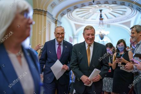 Senate Majority Leader Chuck Schumer, D-N.Y., left center, and Majority Whip Dick Durbin, D-Ill., joined at left by Assistant Majority Leader Patty Murray, D-Wash., Sen. Debbie Stabenow, D-Mich., laugh following a news conference about his plans for a procedural vote tomorrow on the bipartisan infrastructure deal senators brokered with President Joe Biden, at the Capitol in Washington