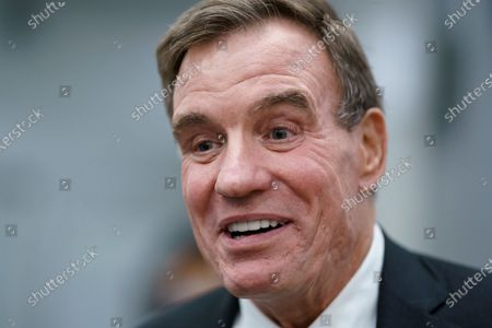 Sen. Mark Warner, D-Va., speaks with reporters as he boards the Senate subway, at the Capitol in Washington