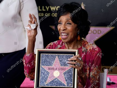 Actress Marla Gibbs celebrates with a replicator's of her new star on the Hollywood Walk of Fame following a ceremony for her, in Los Angeles