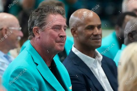 Former Miami Dolphins players Dan Marino, foreground, and Jason Taylor, rear, listen during a ceremony at the NFL football team's new training facility, in Miami Gardens, Fla. The Dolphins held a grand opening for their $135 million training complex one week before the start of training camp