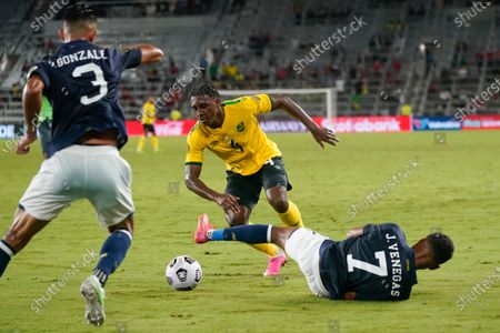 Jamaica defender Amarii Bell (4) tries to get the ball between Costa Rica defender Giancarlo Gonzalez (3) and forward Johan Venegas (7) during the second half of a CONCACAF Gold Cup Group C soccer match, in Orlando, Fla