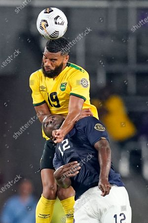 Jamaica defender Adrian Morrison, top, gets position on a head ball over Costa Rica forward Joel Campbell (12) during the second half of a CONCACAF Gold Cup Group C soccer match, in Orlando, Fla