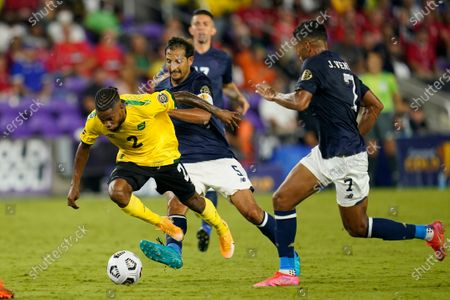 Jamaica midfielder Lamar Walker (2) moves the ball between Costa Rica midfielder Celso Borges (5) and forward Johan Venegas (7) during the second half of a CONCACAF Gold Cup Group C soccer match, in Orlando, Fla