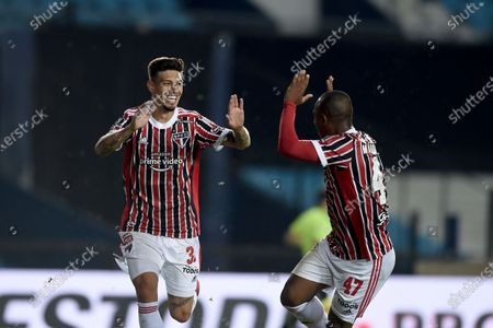 Emiliano Rigoni of Brazil's Sao Paulo, left, is congratulated by teammate Marquinhos after scoring their side's opening goal against Argentina's Racing Club during a Copa Libertadores round of 16 second leg soccer match in Buenos Aires, Argentina