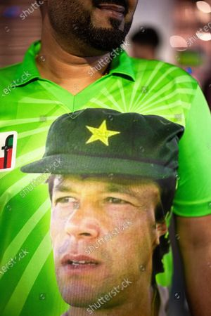 A Pakistan cricket fan wearing a t-shirt featuring a portrait of former cricketer and current Pakistani Prime Minister Imran Khan . Muslims celebrate Eid al-Adha in Rusholme in Manchester. The festival marks the Islamic tale of the prophet Ibrahim , who offered his son as a sacrifice to Allah .