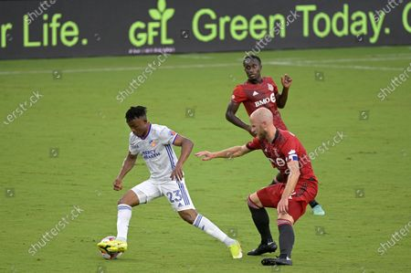 Cincinnati forward Isaac Atanga (23) controls a ball in front of Toronto FC midfielder Michael Bradley, right, and midfielder Richie Laryea, rear, during the first half of an MLS soccer match, in Orlando, Fla