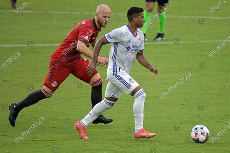 Cincinnati midfielder Allan Cruz, right, controls a ball in front of Toronto FC midfielder Michael Bradley during the first half of an MLS soccer match, in Orlando, Fla