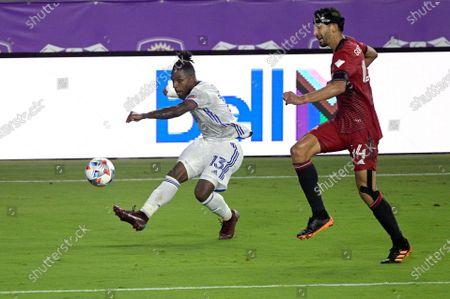 Stock Image of Cincinnati midfielder Joseph-Claude Gyau (13) kicks a ball in front of Toronto FC defender Omar Gonzalez (44) during the second half of an MLS soccer match, in Orlando, Fla