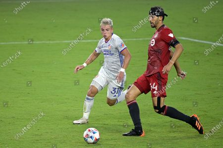 Cincinnati midfielder Alvaro Barreal (31) and Toronto FC defender Omar Gonzalez (44) compete for a ball during the second half of an MLS soccer match, in Orlando, Fla
