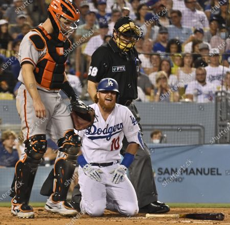 Los Angeles Dodgers' Justin Turner reacts after being hit in the left knee by an 84-mph slider from San Francisco starting pitcher Alex Wood during the third inning at Dodger Stadium in Los Angeles on Tuesday, July 20, 2021. Turner stayed in the game through the fifth before departing. Manager Dave Roberts said Turner won't play Wednesday.