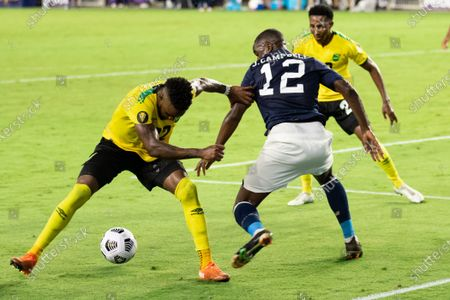 Joel Campbell (12 Costa Rica) gets the ball past Devon Williams (22 Jamaica) during the CONCACAF Gold Cup game between Costa Rica and Jamaica at Exploria Stadium in Orlando, Florida.
