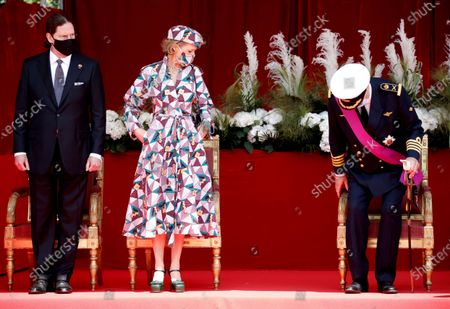 Belgium's Princess Delphine, center, her husband James O'Hare, left, and Belgium's Prince Laurent, right, take their places on the Royal tribune prior to the National Day parade in Brussels, . Belgium celebrates its National Day on Wednesday in a scaled down version due to coronavirus, COVID-19 measures