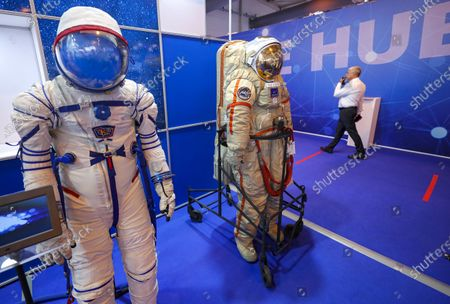 Stock Picture of A woman passes the new prototype of the Sokol-M (L) promising rescue spacesuit for the crew of the future Russian manned spacecraft 'Orel' and 'Orlan' (C) a series of semi-rigid one-piece space suit models designed and built by NPP Zvezda at the MAKS 2021 International Aviation and Space Salon in Zhukovsky outside Moscow, Russia, 21 July 2021. The Orlan spacesuit was used for Russian EVA's on Salyut, Mir, and the International Space Station. The International Aviation and Space Salon MAKS 2021 take place from 20 to 25 July.