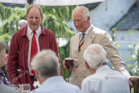 Britain's Prince Charles with Michael Morpurgo, left, attend a lunch club for local residents, the first since the pandemic began, at the Duke of York Inn in Iddesleigh, south west England