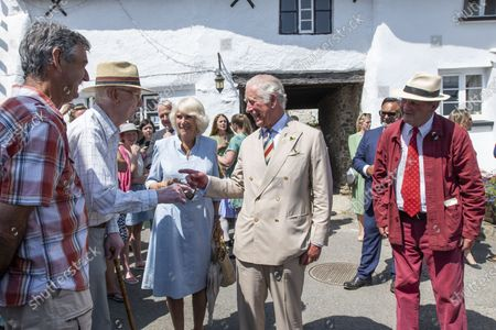 Britain's Prince Charles and Camilla, Duchess of Cornwall with Michael Morpurgo, right, attend a lunch club for local residents, the first since the pandemic began, at the Duke of York Inn in Iddesleigh, south west England