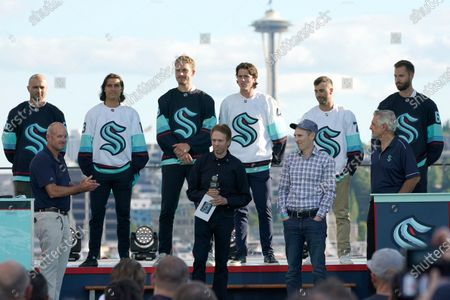 New Seattle Kraken NHL hockey players, back row from left, Mark Giordano, Brandon Tanev, Jamie Oleksiak, Hadyn Fluery, Jordan Eberle and Chris Dreidger stand on stage with Kraken owners David Wright, front left, Jerry Bruckheimer, front center, and Andy Jassy, front second from right, and Kraken general manager Ron Francis, front right, after being introduced during the Kraken's expansion draft event in Seattle. Jassy is also president and CEO of Amazon.com