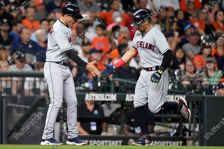 Stock Image of Cleveland Indians' Cesar Hernandez, right, clasps hands with third base coach Mike Sarbaugh after hitting a solo home run during the seventh inning of the team's baseball game against the Houston Astros, in Houston