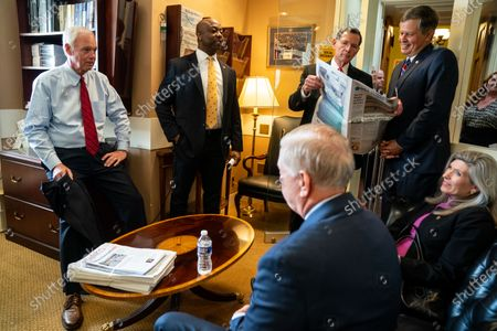 (L to R) Sen. Ron Johnson (R-WI), Sen. Tim Scott (R-SC), Sen. John Barrasso (R-WY), Sen. Steve Daines, Sen. Lindsey Graham (R-SC), center, and Sen. Joni Ernst (R-IA) talk with each other before a news conference on Capitol Hill on Wednesday, July 21, 2021. (Kent Nishimura / Los Angeles Times)