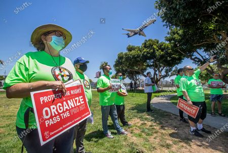 Nicole Moore, left, a driver for Lyft, joins other rideshare drivers during a rally at LAX Airport Landing Viewpoint in Los Angeles. They were taking part in a strike aimed to push congress to pass the protect the right to organize act, proposed federal legislation that allows contractors to unionize if they choose. Moore said that she stopped driving for Lyft once the pandemic started because she didn't think it was safe to continue. (Mel Melcon / Los Angeles Times)