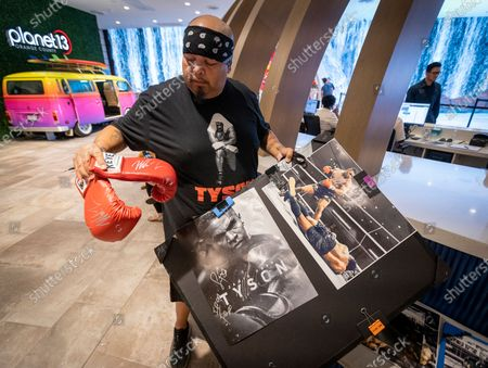 Ace Sanchez, of Hemet, views his gloves and photos that he got signed by former heavyweight champion and cannabis entrepreneur Mike Tyson, who signed autographs and took photos with fans while promoting his Tyson Ranch brand at Planet 13 dispensary in Santa Ana on Wednesday, July 21, 2021. (Allen J. Schaben / Los Angeles Times)