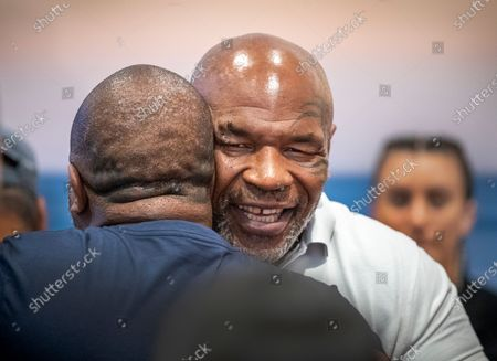 Former heavyweight champion and cannabis entrepreneur Mike Tyson hugs Rafael Cordeiro, a coach at Kings MMA of Huntington Beach, while signing autographs and taking photos with fans and promoting his Tyson Ranch brand at Planet 13 dispensary in Santa Ana on Wednesday, July 21, 2021. (Allen J. Schaben / Los Angeles Times)
