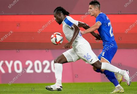 Stock Photo of Honduras's Jose Garcia, left, and Alexandru Dobre of Romania battle for the ball during a men's soccer match at the 2020 Summer Olympics, in Kashima, Japan