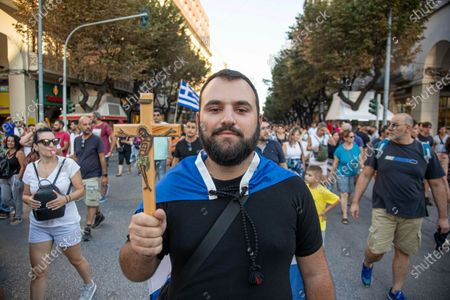 A young male protester is holding a cross with Jesus and carrying the Greek Flag during the Demonstration Against  The Mandatory Vaccine was held in Thessaloniki and Athens in Greece on Wednesday July 21, 2021. One week after the massive protest against the mandatory vaccination the anti-vaxx campaign continues with a big group protesting in the streets of the city of Thessaloniki. The protest was organized via social media by anti-vaccination believers. According to the group more than 40.000 people participated, while the police estimated unofficially slightly around 15.000 people participating in the demonstration. As the Greek government is passing a legislation with mandatory vaccination to specific job sectors like medical healthcare workers etc people are protesting against it. Protesters marched in the center of Thessaloniki where car traffic was stopped for a couple of hours. Nationalists and religious groups supported the demo spelling many slogans against the Prime Minister Mitsotakis and Journalists. The demonstration ended at the statue of Alexander the Great while it began from the White Tower, symbol of the city. Riot police monitored the event carefully with a distance to avoid violent incidents from radicals. Greece is having a surge in COVID-19 Coronavirus cases as the pandemic rises again due to the Delta Mutation variant and the peaking in the vaccination program, applying some local lockdowns to areas like the Greek Islands. Thessaloniki, Greece on July 21, 2021