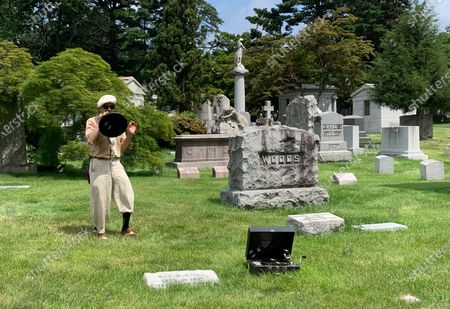 """Stock Image of Michael Cumella, aka DJ MAC, speaks through a vintage megaphone near the gravesite of Nat M. Wills, a vaudeville star of the early 20th century known as """"The Happy Tramp"""" at Woodlawn Cemetery in the Bronx on . Wills was among the jazz and vaudeville greats included on a tour led by Cumella"""