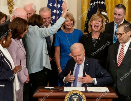 Stock Image of President Joe Biden reacts as Sen. Dianne Feinstein, D-Calif., third from left, raises her hand after she isn't given a pen after the president signs H.R. 1652, the VOCA Fix to Sustain the Crime Victims Fund Act of 2021, in the East Room of the White House in Washington, . Also pictured from left, Rep. Sheila Jackson Lee, D-Texas, Vice President Kamala Harris, Sen. Chris Van Hollen, D-Md., Sen. Lisa Murkowski, R-Alaska, Sen. Tammy Baldwin, D-Wis., Rep. Brian Fitzpatrick, R-Pa., and Rep. Jerrold Nadler, D-N.Y