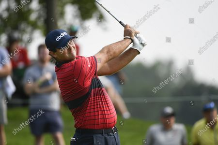 Patrick Reed watches his tee shot on the eighth hole during the first round of the 3M Open golf tournament in Blaine, Minn