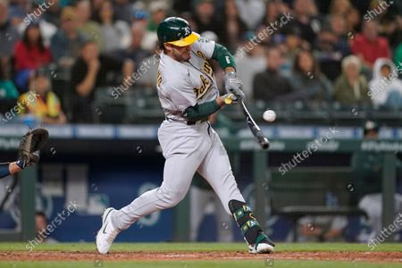 Oakland Athletics' Ramon Laureano hits a single to score Matt Chapman during the eighth inning of athe team's baseball game against the Seattle Mariners, in Seattle