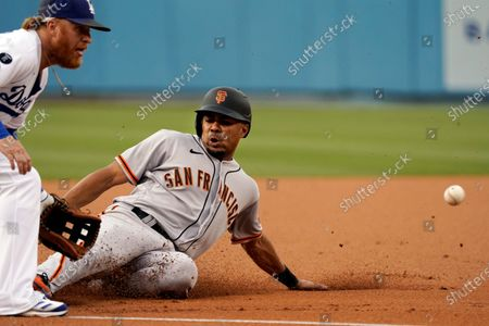 San Francisco Giants' LaMonte Wade Jr., right, steals third base next to Los Angeles Dodgers third baseman Justin Turner during the first inning of a baseball game, in Los Angeles