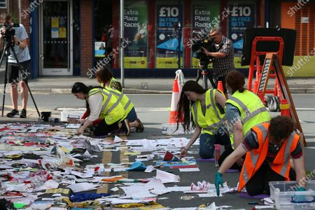 University of Manchester students carefully remove messages left at the mural of Marcus Rashford in Manchester. The messages are to be taken away for preservation, amid worries that they will disintegrate in the rain.