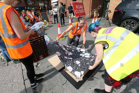 Conservation professionals carefully remove messages left at the mural of Marcus Rashford in Manchester. The messages are to be taken away for preservation, amid worries that they will disintegrate in the rain.