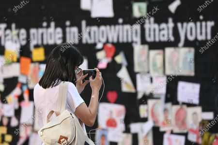 People take photographs of messages left on the mural of Marcus Rashford in Withington, Manchester. The messages are to be removed to Manchester Central Library for preservation.