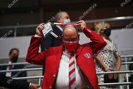 Prince Albert II of Monaco takes off his ID as he arrives during the opening ceremony in the Olympic Stadium at the 2020 Summer Olympics, in Tokyo, Japan