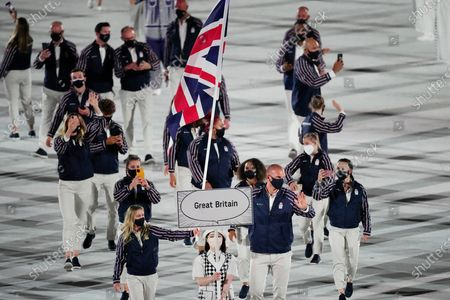 Hannah Mills and Mohamed Sbihi, of Britain, carry their country's flag during the opening ceremony in the Olympic Stadium at the 2020 Summer Olympics, in Tokyo, Japan