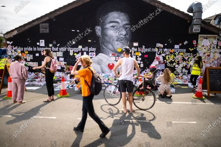 """Volunteers and staff from the Institute for Cultural Practices at Manchester University , Manchester Art Gallery and the People's History Museum work to clean up and salvage tributes left at a memorial that grew up around a mural to England footballer Marcus Rashford , after storms and heavy rain hit the region overnight . The mural , painted by local artist """" Akse P19 """" on the side of a cafe in Withington , was defaced after England's loss to Italy on penalties in the final of the European Cup , prompting support for England's black players and anger towards the racism that had been shown towards those black players , following the match ."""