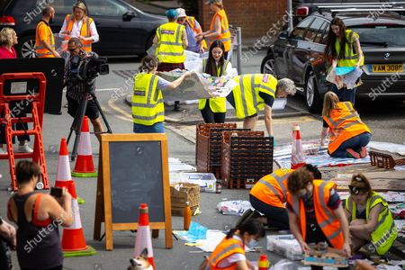 """Stock Picture of Volunteers and staff from the Institute for Cultural Practices at Manchester University , Manchester Art Gallery and the People's History Museum work to clean up and salvage tributes left at a memorial that grew up around a mural to England footballer Marcus Rashford , after storms and heavy rain hit the region overnight . The mural , painted by local artist """" Akse P19 """" on the side of a cafe in Withington , was defaced after England's loss to Italy on penalties in the final of the European Cup , prompting support for England's black players and anger towards the racism that had been shown towards those black players , following the match ."""