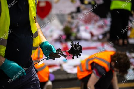 """Stock Image of Volunteers and staff from the Institute for Cultural Practices at Manchester University , Manchester Art Gallery and the People's History Museum work to clean up and salvage tributes left at a memorial that grew up around a mural to England footballer Marcus Rashford , after storms and heavy rain hit the region overnight . The mural , painted by local artist """" Akse P19 """" on the side of a cafe in Withington , was defaced after England's loss to Italy on penalties in the final of the European Cup , prompting support for England's black players and anger towards the racism that had been shown towards those black players , following the match ."""